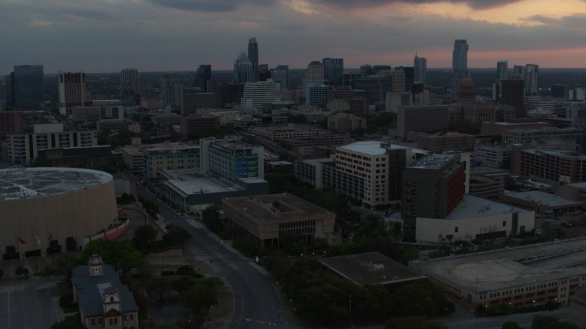 5.7K aerial video reverse view of hospital, skyscrapers and capitol dome at sunset in Downtown Austin, Texas Aerial Stock Footage | DX0002_105_018