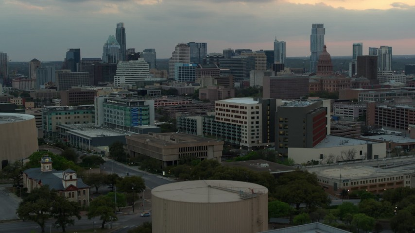 5.7K aerial video ascend for view of hospital, skyscrapers and capitol dome at sunset in Downtown Austin, Texas Aerial Stock Footage | DX0002_105_021