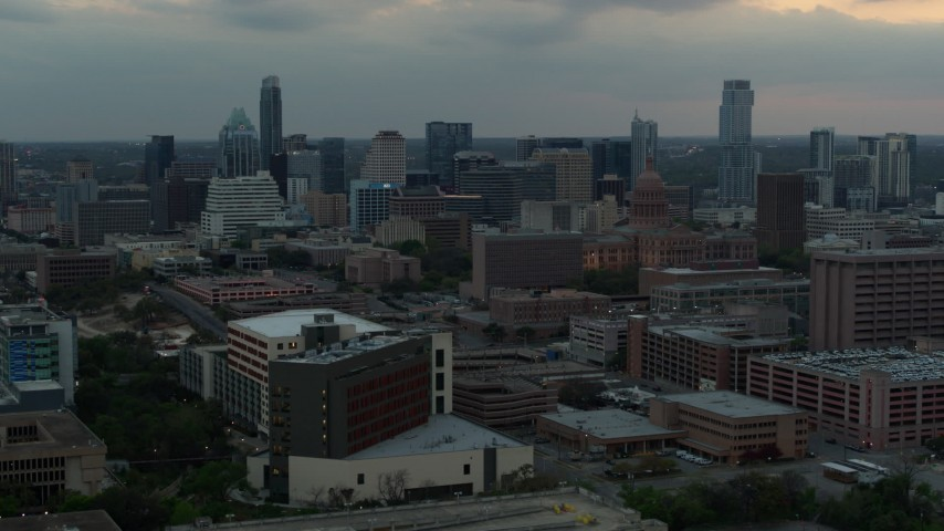 5.7K aerial video office buildings around capitol dome at sunset, skyscrapers in background in Downtown Austin, Texas Aerial Stock Footage DX0002_105_022