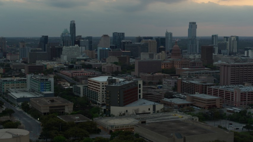 5.7K stock footage aerial video of office buildings and capitol dome at sunset, skyscrapers in distance in Downtown Austin, Texas Aerial Stock Footage | DX0002_105_023