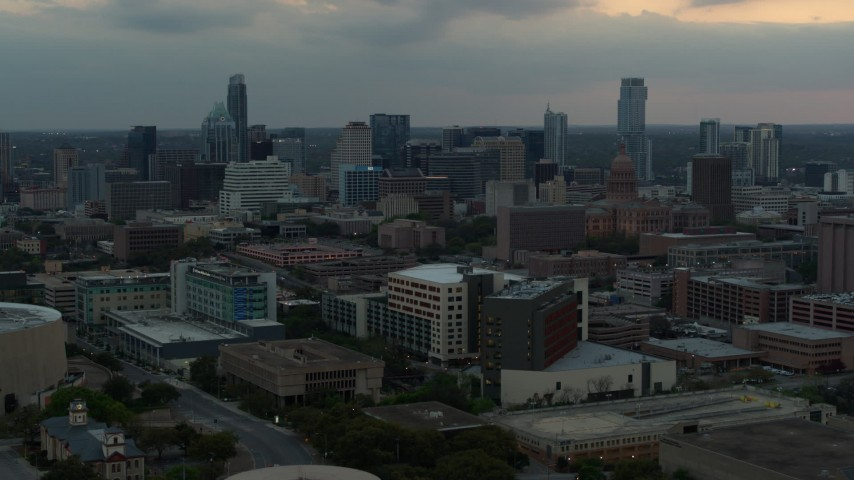 5.7K stock footage aerial video approach hospital, skyscrapers and capitol dome in distance at sunset in Downtown Austin, Texas Aerial Stock Footage | DX0002_105_024