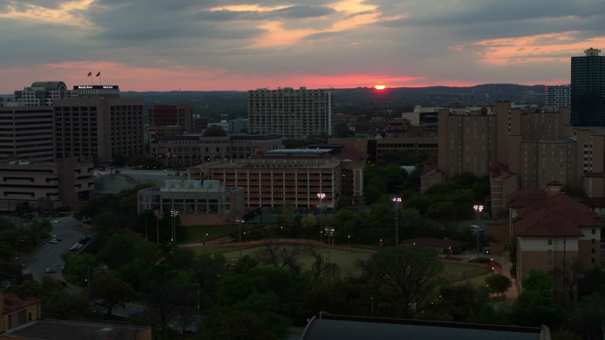 5.7K stock footage aerial video of the distant setting sun while flying past the university, Austin, Texas Aerial Stock Footage | DX0002_105_028