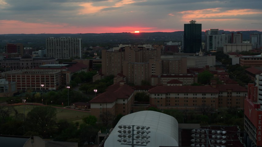 5.7K stock footage aerial video of flying by the university campus with setting sun in distance, Austin, Texas Aerial Stock Footage | DX0002_105_029
