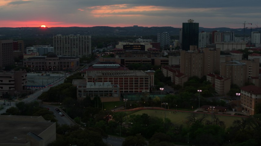 5.7K stock footage aerial video of ascending by the university campus with setting sun in distance, Austin, Texas Aerial Stock Footage | DX0002_105_031