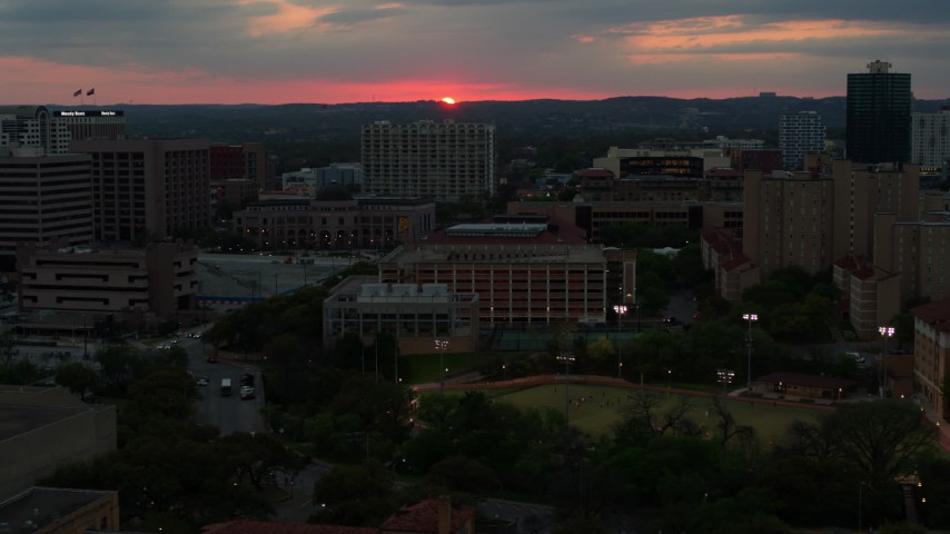 5.7K stock footage aerial video slowly passing by the university campus with setting sun in distance, Austin, Texas Aerial Stock Footage | DX0002_105_032