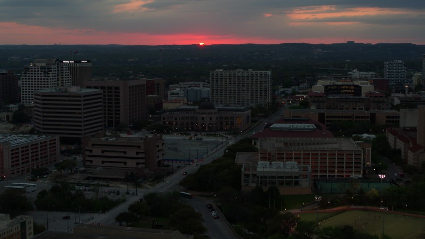 5.7K stock footage aerial video stationary view of setting sun before flying by university campus, Austin, Texas Aerial Stock Footage | DX0002_105_034
