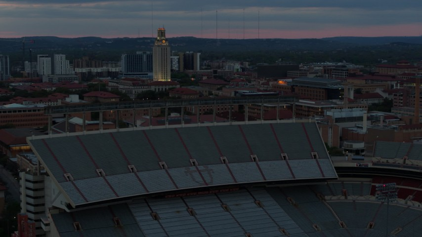 5.7K stock footage aerial video of UT Tower and football stadium at the University of Texas at twilight, Austin, Texas Aerial Stock Footage | DX0002_105_036