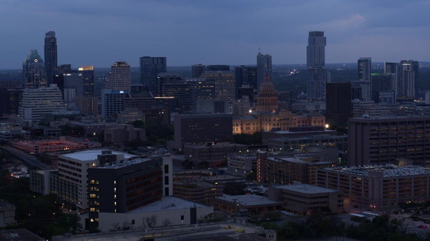5.7K aerial video a view of office buildings around capitol at twilight, skyscrapers in background in Downtown Austin, Texas Aerial Stock Footage | DX0002_105_041