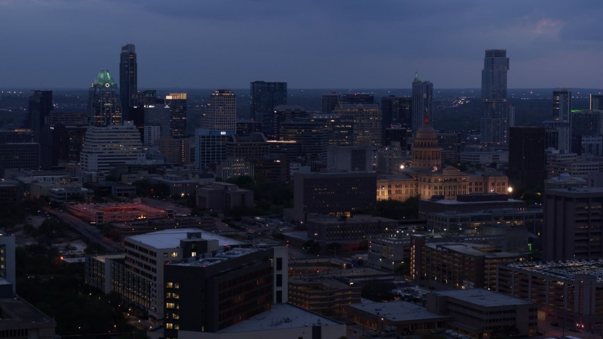 5.7K stock footage aerial video of passing by office buildings, capitol and skyscrapers at twilight in Downtown Austin, Texas Aerial Stock Footage | DX0002_105_045