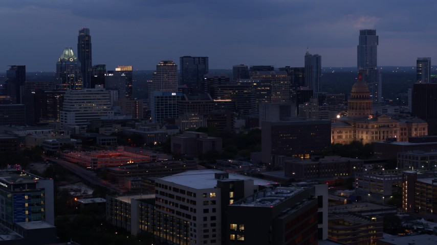 5.7K aerial video of descending by office buildings, capitol and skyscrapers at twilight in Downtown Austin, Texas Aerial Stock Footage | DX0002_105_047