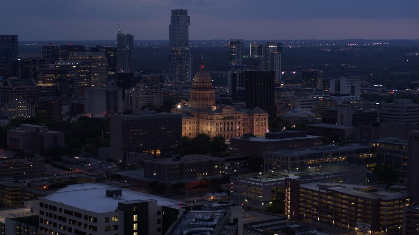 5.7K stock footage aerial video of the state capitol lit up at twilight, office buildings and skyscrapers in Downtown Austin, Texas Aerial Stock Footage | DX0002_105_051