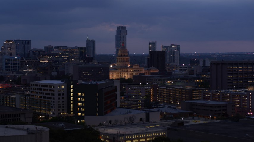 5.7K aerial video descend near office buildings with view of state capitol at twilight in Downtown Austin, Texas Aerial Stock Footage | DX0002_105_052