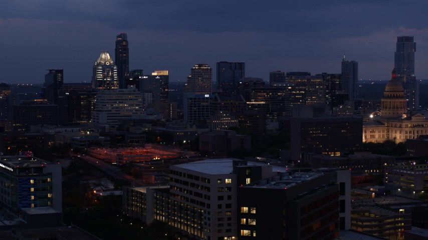 5.7K aerial video descend with view of office buildings, skyscrapers near capitol at twilight in Downtown Austin, Texas Aerial Stock Footage | DX0002_105_054