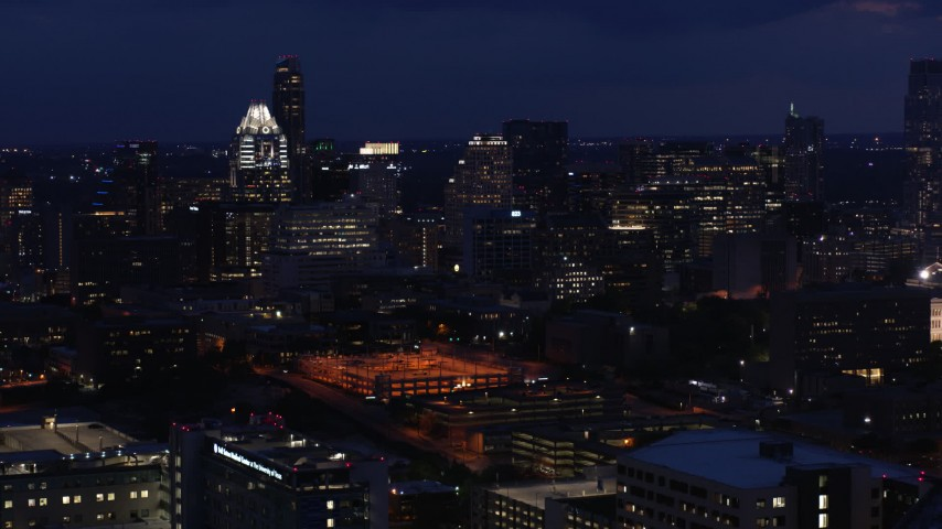 5.7K aerial video approach office buildings and skyscrapers at night in Downtown Austin, Texas Aerial Stock Footage | DX0002_106_001