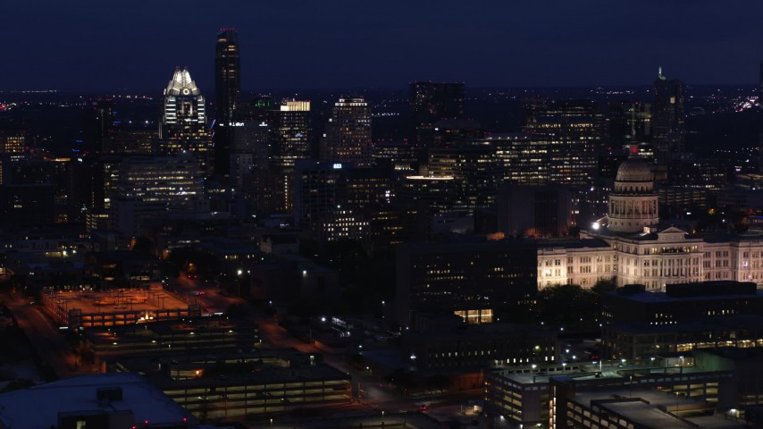 5.7K aerial video flyby office buildings and skyscrapers at night, reveal capitol in Downtown Austin, Texas Aerial Stock Footage DX0002_106_002