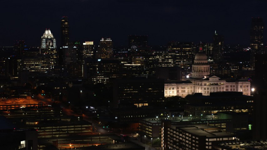5.7K stock footage aerial video of skyscrapers and office buildings behind the Texas State Capitol at night in Downtown Austin, Texas Aerial Stock Footage | DX0002_106_011