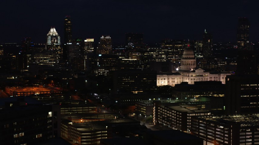 5.7K aerial video flyby skyscrapers and office buildings behind Texas State Capitol at night in Downtown Austin, Texas Aerial Stock Footage | DX0002_106_012
