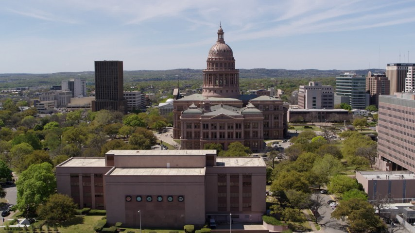 5.7K stock footage aerial video descend behind library with view of Texas State Capitol in Downtown Austin, Texas Aerial Stock Footage | DX0002_107_012
