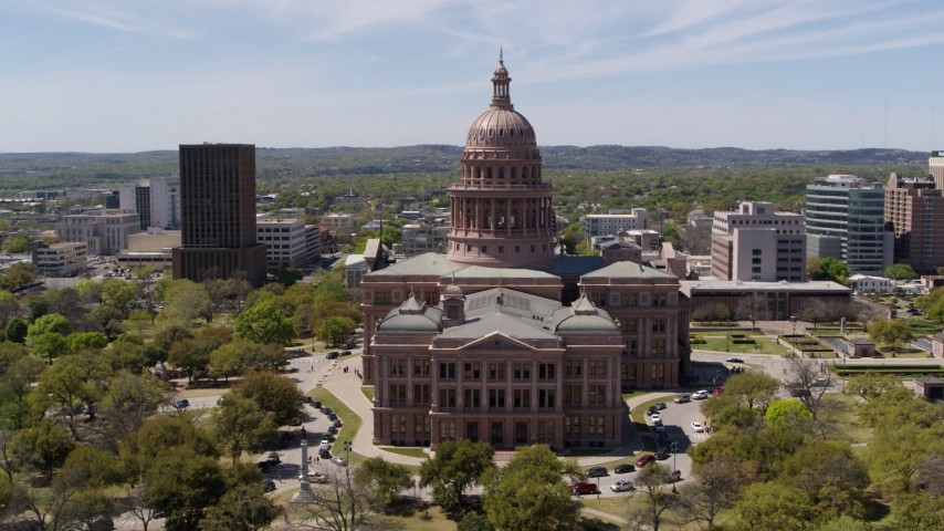 5.7K aerial video ascend over library for view of Texas State Capitol in Downtown Austin, Texas Aerial Stock Footage DX0002_107_013
