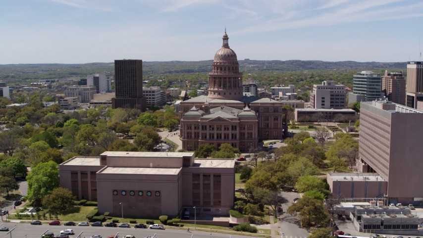 5.7K stock footage aerial video descend by library and orbit the Texas State Capitol dome and grounds in Downtown Austin, Texas Aerial Stock Footage | DX0002_107_017