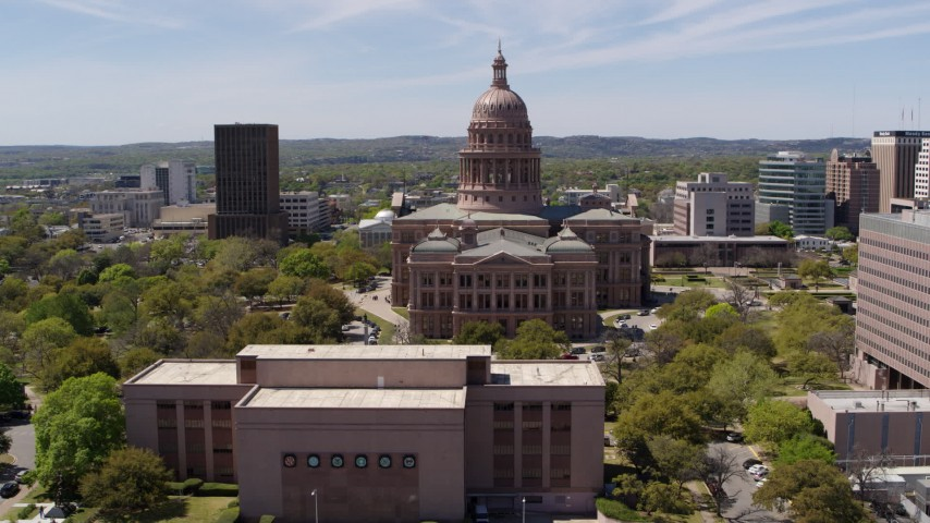 5.7K stock footage aerial video reverse view of Texas State Capitol, reveal library in Downtown Austin, Texas Aerial Stock Footage | DX0002_107_019