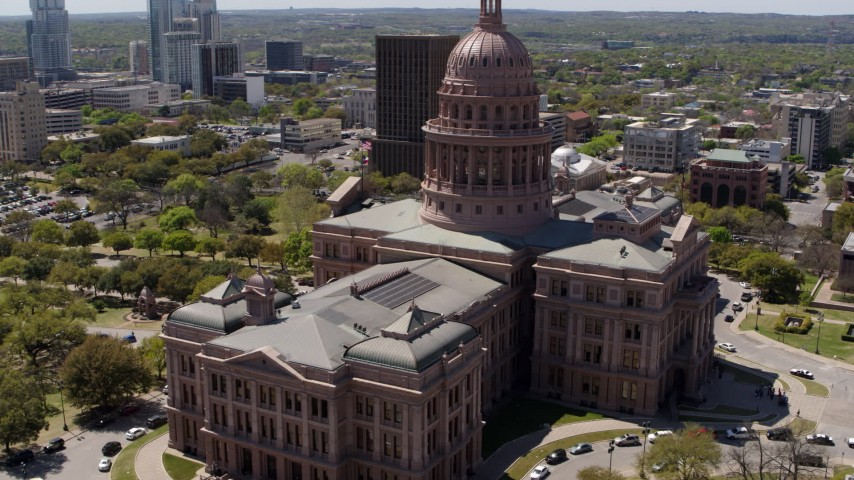 5.7K stock footage aerial video orbit the Texas State Capitol building before flying away in Downtown Austin, Texas Aerial Stock Footage | DX0002_107_021