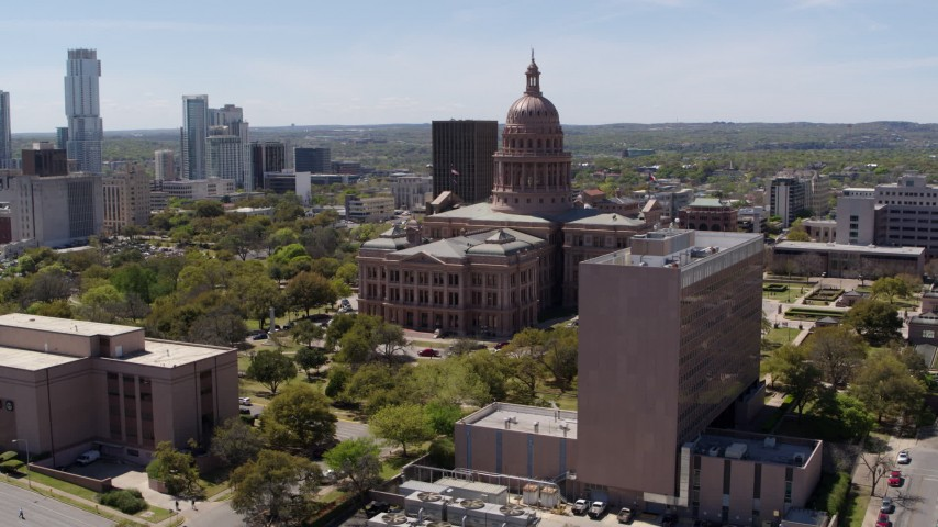5.7K stock footage aerial video of fly away from the Texas State Capitol, descend near government office building in Downtown Austin, Texas Aerial Stock Footage | DX0002_107_023