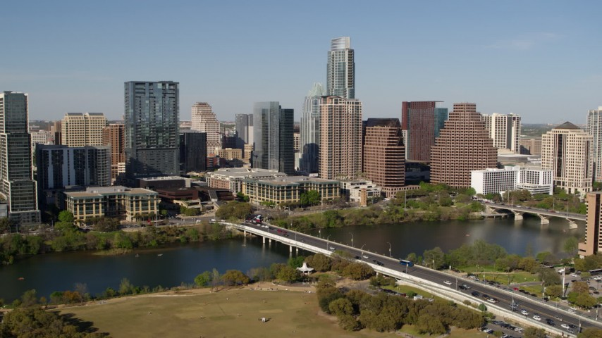 5.7K aerial video of the city's skyline across Lady Bird Lake, ascend near bridge, Downtown Austin, Texas Aerial Stock Footage | DX0002_109_001
