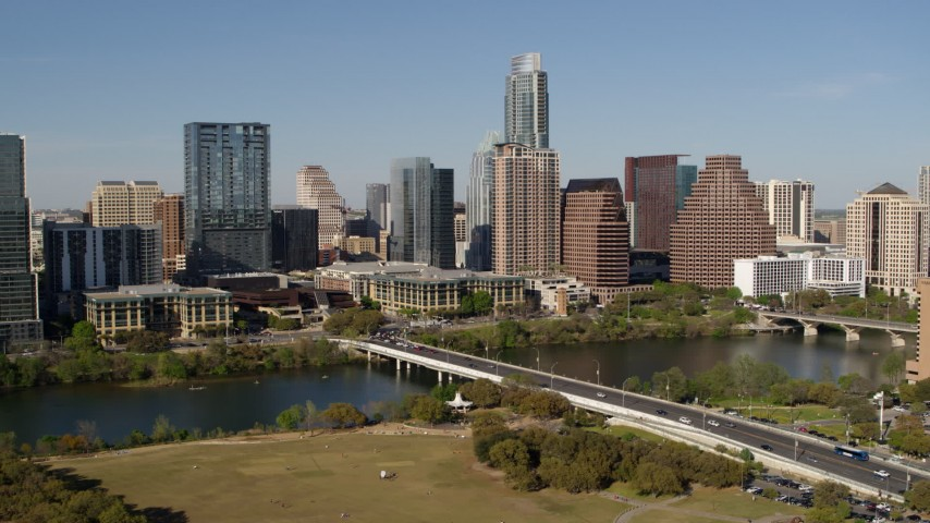 5.7K stock footage aerial video focus on the city's skyline across Lady Bird Lake, ascend near bridge, Downtown Austin, Texas Aerial Stock Footage DX0002_109_004 | Axiom Images