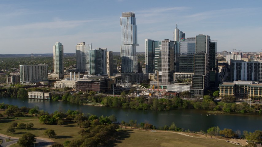 5.7K aerial video modern skyscraper on the other side of Lady Bird Lake, Downtown Austin, Texas Aerial Stock Footage | DX0002_109_007