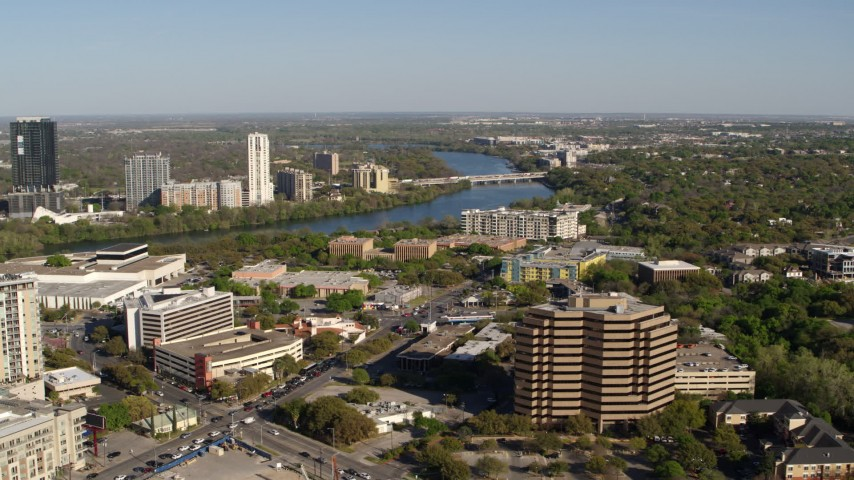 5.7K stock footage aerial video a freeway bridge spanning Lady Bird Lake, descend near office building, Austin, Texas Aerial Stock Footage | DX0002_109_009