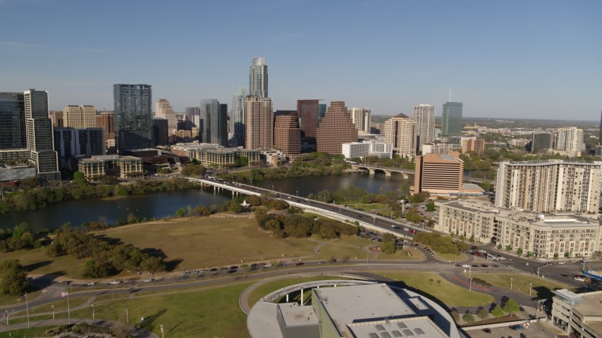 5.7K aerial video a reverse view of the city's waterfront skyline and First Street Bridge over Lady Bird Lake, Downtown Austin, Texas Aerial Stock Footage | DX0002_109_023