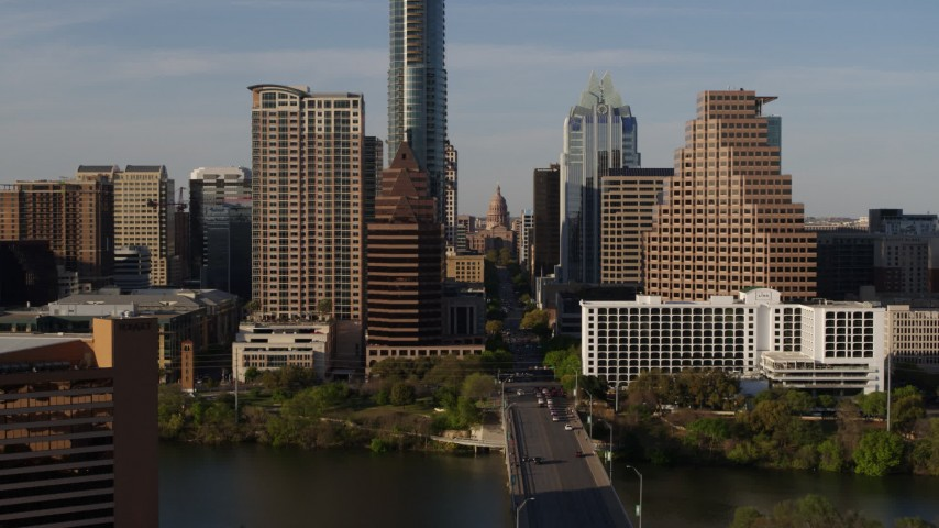 5.7K stock footage aerial video of the Texas State Capitol seen between skyscrapers in Downtown Austin, Texas Aerial Stock Footage | DX0002_109_029