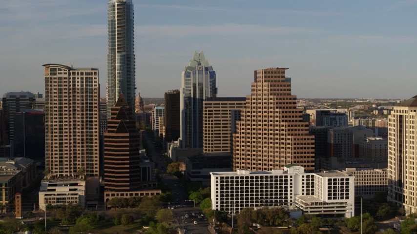 5.7K stock footage aerial video passing downtown skyscrapers and reveal the state capitol in Downtown Austin, Texas Aerial Stock Footage | DX0002_109_035