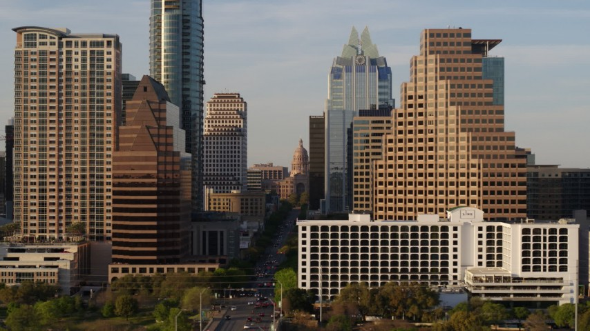 5.7K stock footage aerial video of the state capitol building seen between skyscrapers in Downtown Austin, Texas Aerial Stock Footage | DX0002_109_038