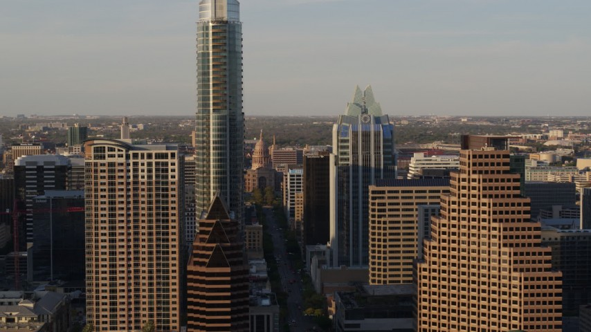 5.7K stock footage aerial video flying by skyscrapers to reveal Texas State Capitol in Downtown Austin, Texas Aerial Stock Footage | DX0002_109_041