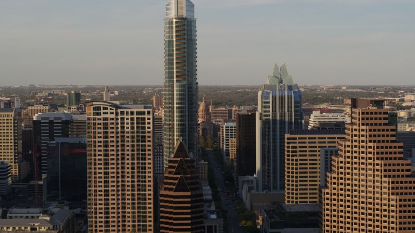 5.7K aerial video fly between downtown skyscrapers, reveal Texas State Capitol in Downtown Austin, Texas Aerial Stock Footage | DX0002_109_042