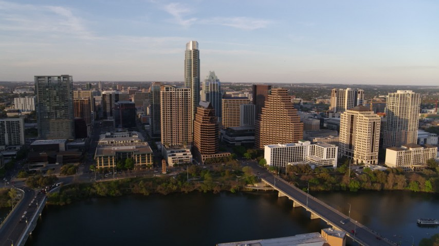 5.7K aerial video of waterfront skyscrapers across Lady Bird Lake at sunset in Downtown Austin, Texas Aerial Stock Footage | DX0002_110_004