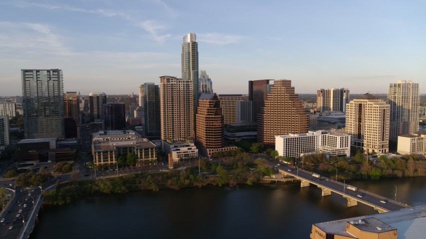 5.7K aerial video of waterfront skyscrapers across Lady Bird Lake at sunset in Downtown Austin, Texas during descent Aerial Stock Footage | DX0002_110_005