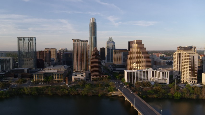 5.7K stock footage aerial video of a view of waterfront skyscrapers across Lady Bird Lake at sunset in Downtown Austin, Texas Aerial Stock Footage | DX0002_110_006