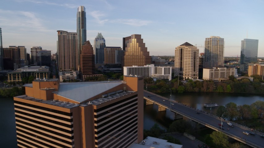 5.7K stock footage aerial video fly away from waterfront skyscrapers across Lady Bird Lake at sunset, reveal hotel in Downtown Austin, Texas Aerial Stock Footage | DX0002_110_007