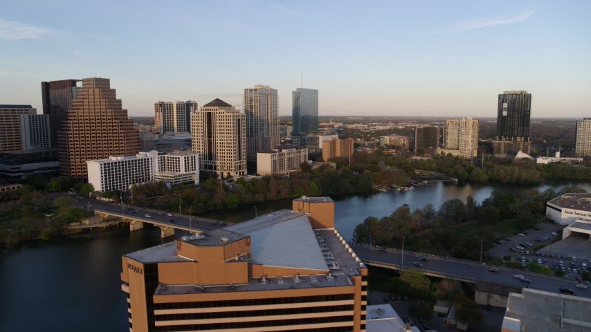 5.7K stock footage aerial video fly over hotel toward waterfront skyscrapers and Lady Bird Lake at sunset, Downtown Austin, Texas Aerial Stock Footage | DX0002_110_008