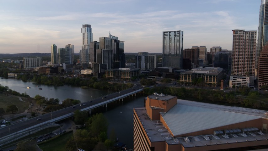 5.7K aerial video fly away from skyline and Lady Bird Lake at sunset, reveal hotel in Downtown Austin, Texas Aerial Stock Footage | DX0002_110_009