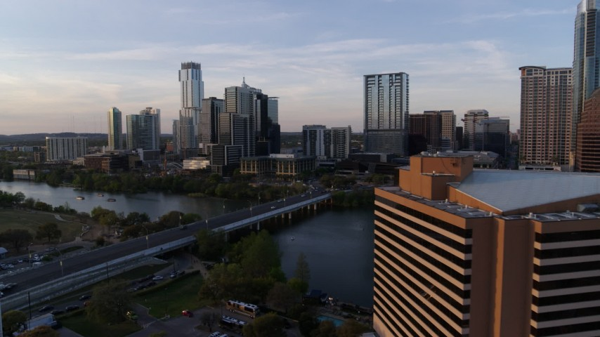 5.7K stock footage aerial video flyby hotel to approach skyline and Lady Bird Lake at sunset, Downtown Austin, Texas Aerial Stock Footage | DX0002_110_010