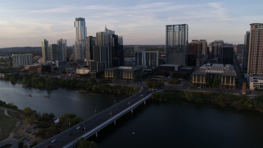 5.7K stock footage aerial video of the city's skyline, and bridge spanning Lady Bird Lake at sunset, Downtown Austin, Texas Aerial Stock Footage | DX0002_110_011