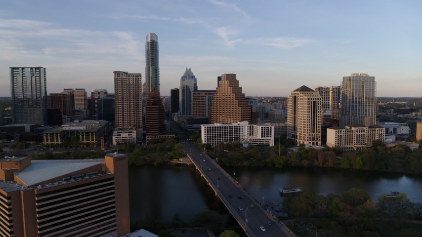 5.7K stock footage aerial video of flying away from skyline across bridge and Lady Bird Lake at sunset in Downtown Austin, Texas Aerial Stock Footage | DX0002_110_012