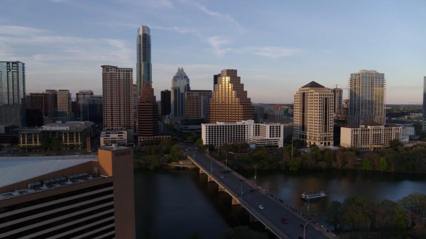5.7K aerial video fly away from skyline, and bridge over Lady Bird Lake at sunset in Downtown Austin, Texas Aerial Stock Footage | DX0002_110_015