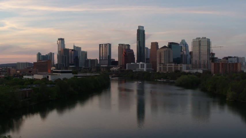 5.7K stock footage aerial video of the city's skyline seen from low over Lady Bird Lake at sunset in Downtown Austin, Texas Aerial Stock Footage | DX0002_110_016