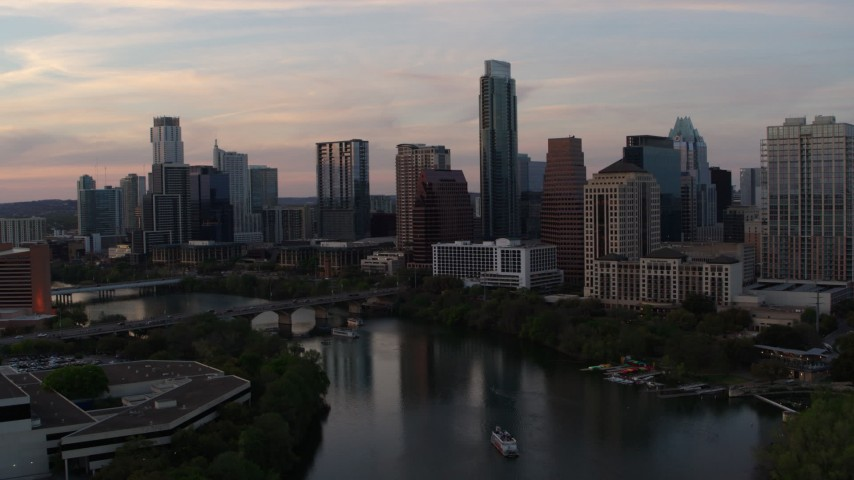 5.7K stock footage aerial video of ascending over Lady Bird Lake toward the skyline at sunset in Downtown Austin, Texas Aerial Stock Footage | DX0002_110_017