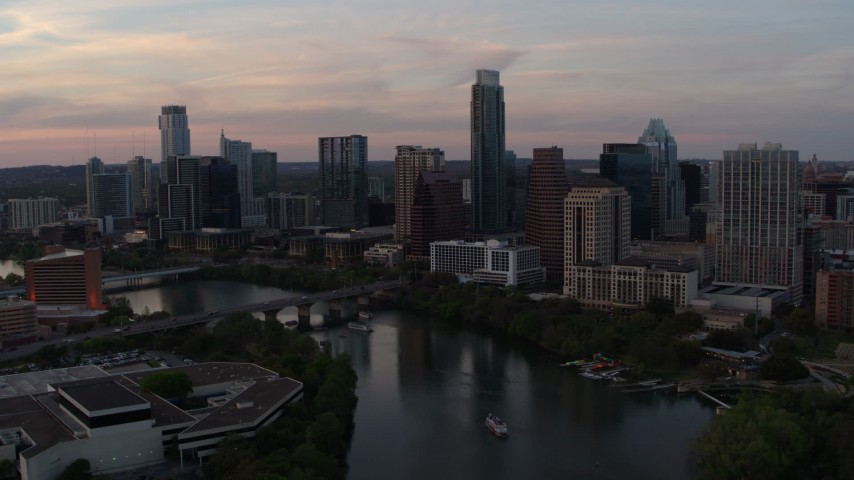 5.7K stock footage aerial video of a reverse view of the skyline from over Lady Bird Lake at sunset in Downtown Austin, Texas Aerial Stock Footage | DX0002_110_018